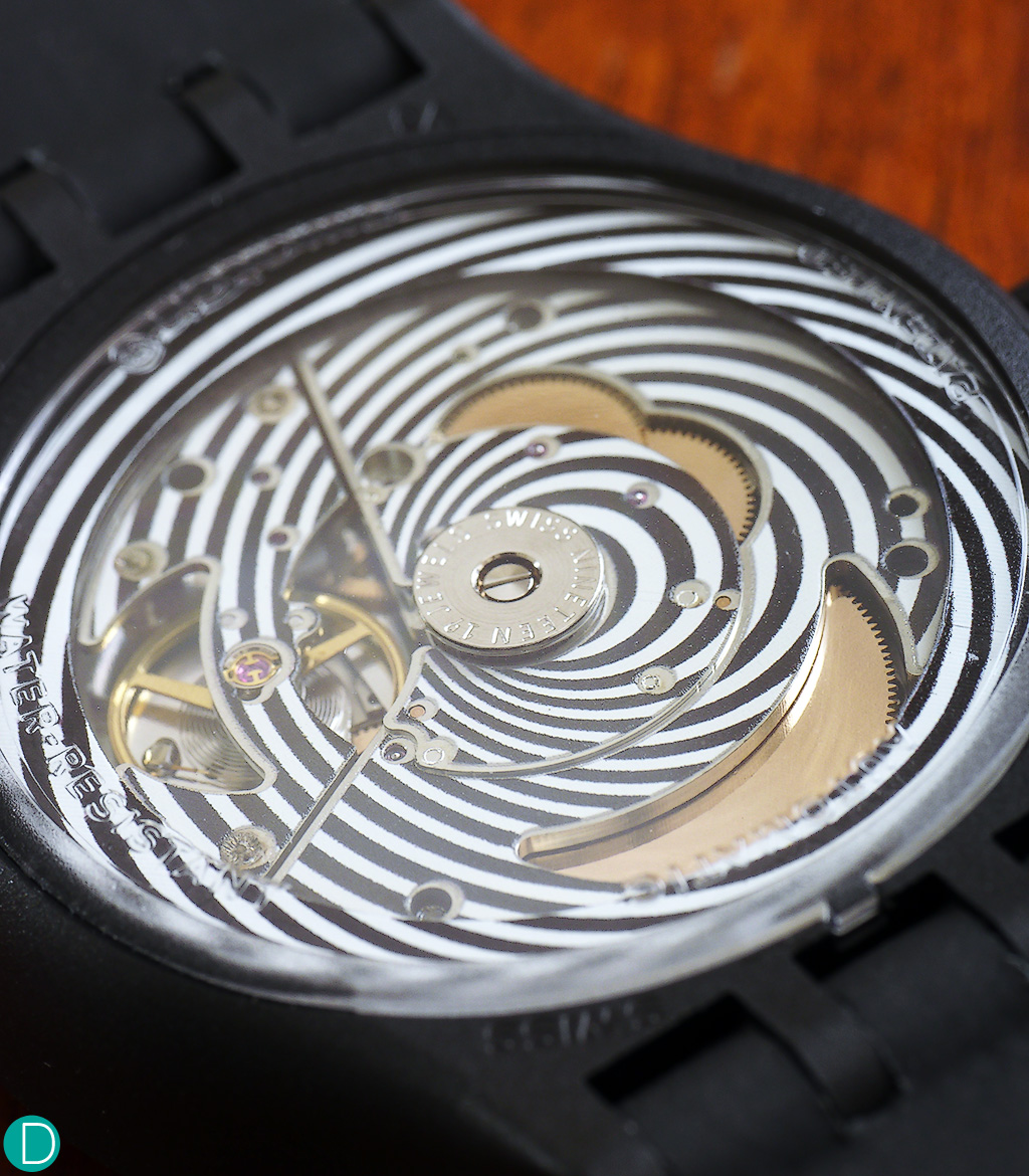Swatch Sistem 51, black, view of the display case back showing the transparent rotor and psychedelic patterns on the movement.