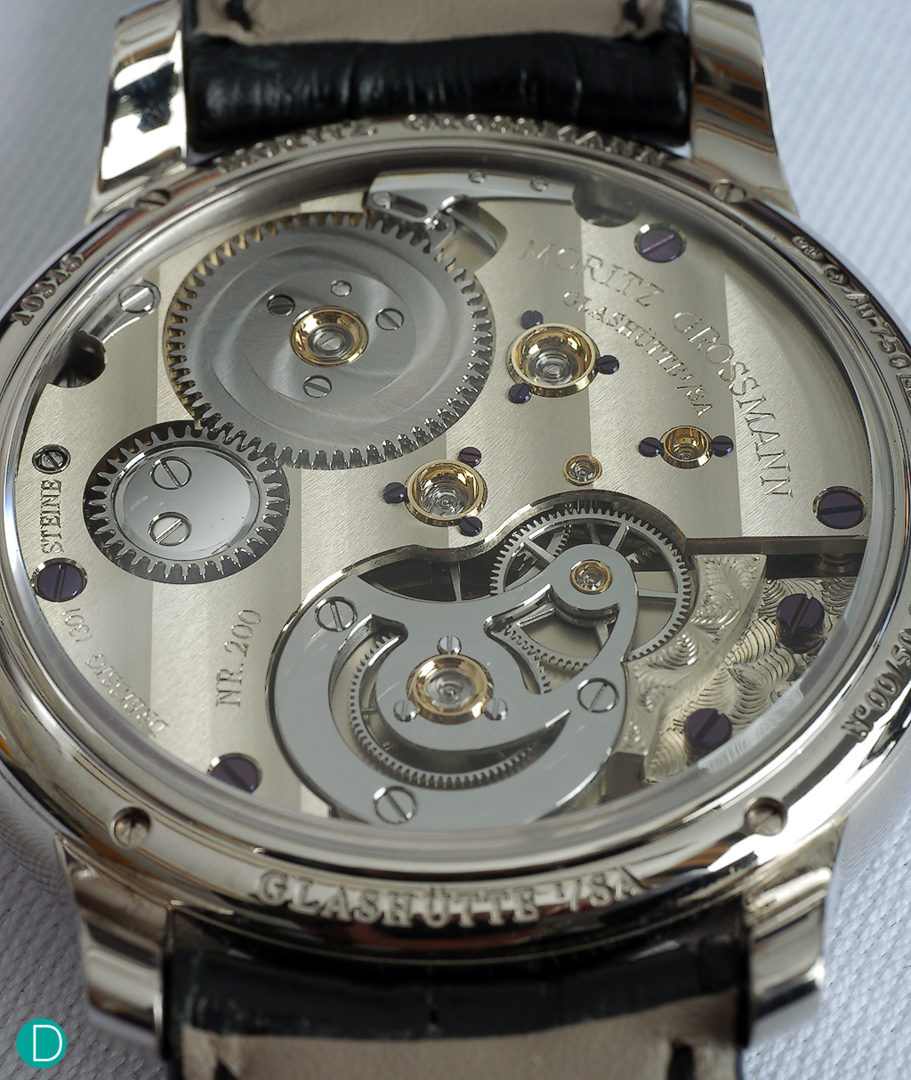 The caliber 103.0 in unfinished German Silver, but with the gear train in ultra modern ARCAP.  The movement is finished with wide Glashütte ribbing, and hand engraved details.
