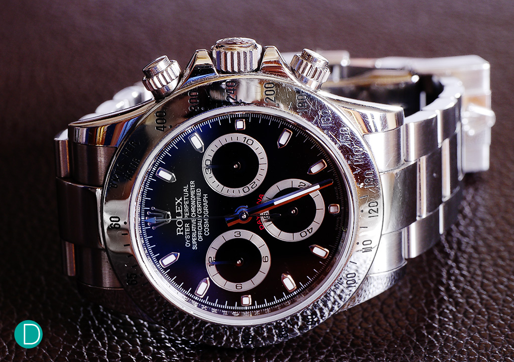 The Rolex Daytona, Ref 116520. This example is cased in stainless steel, and it features a black dial.