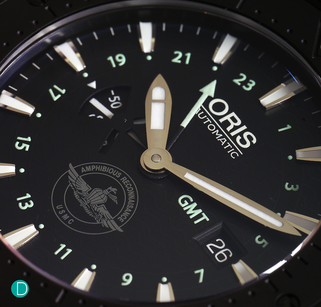Oris Recon GMT dial detail. While the dial looks plain black, it is not. Waves, a subtle reminder that the Marines are part of the US Navy and the USMC logo.