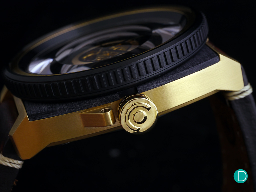 The bezel has a corrugated style finish on its side, a design cue taken from the focusing ring of a lens. The crown comes with one crown guard on the lower side, and is engraved with a logo. On the other side of the case, the model number is carried as a plate inserted into the case side.